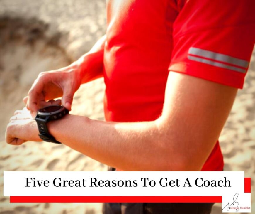 Man with red top looking at his running watch on a beach with a title Five Great Reasons To Get A Coach