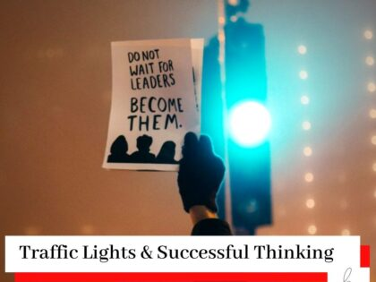Person with a glove holding up a sign reading 'Do not wait for leaders become them' in front a set of traffic lights showing green with the title Traffic Lights & Successful Thinking