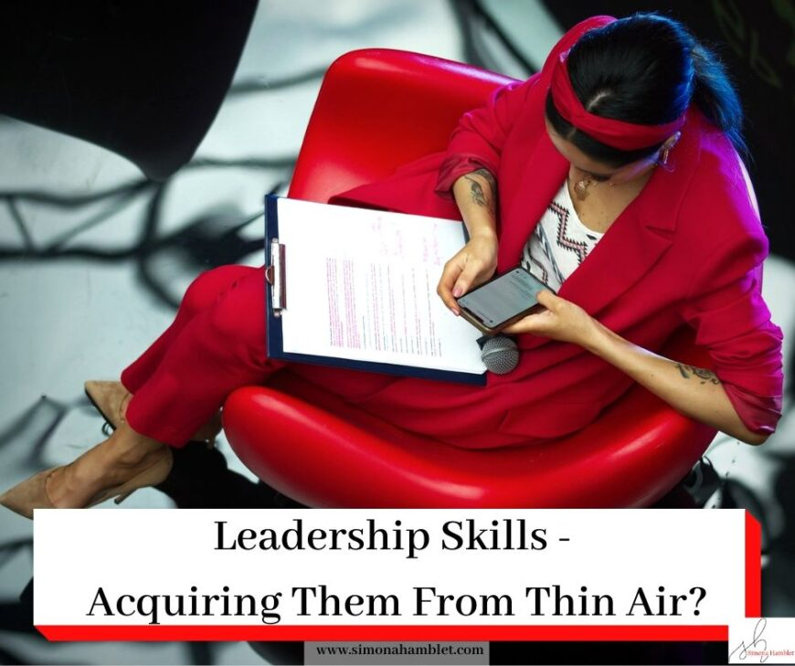 Woman in red sat in a chair with a clipboard and a mobile phone along with the article title Leadership Skills - Acquiring Them From Thin Air?